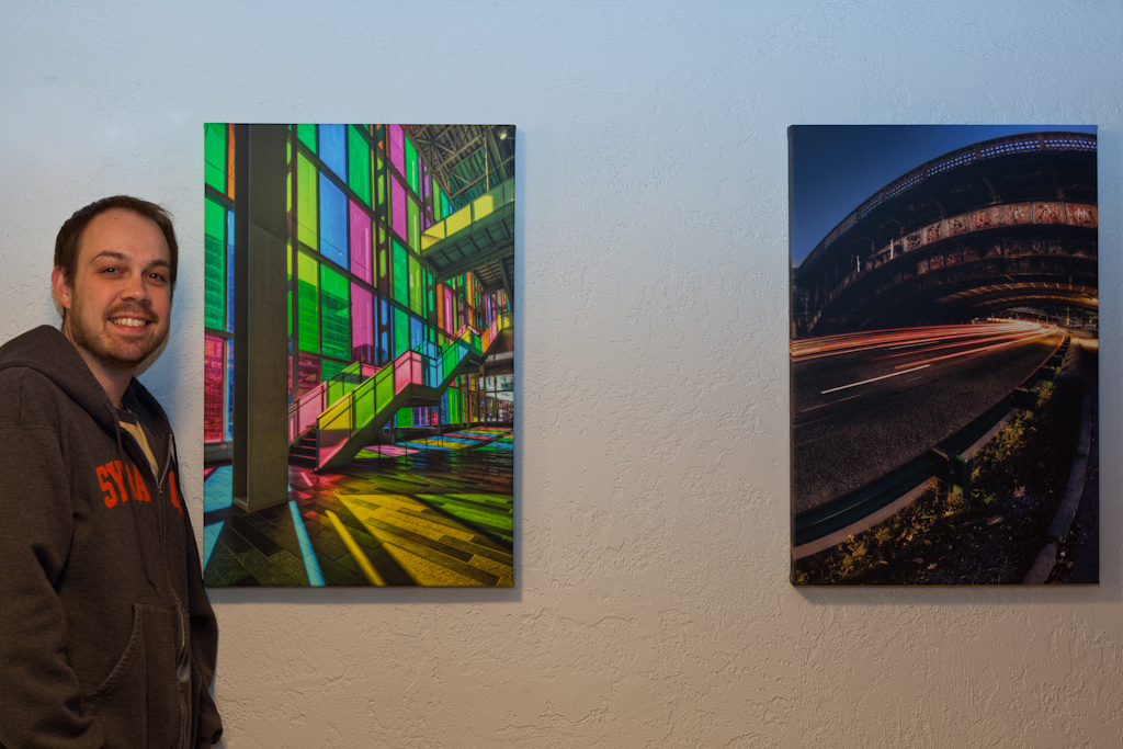 Urban architecture photographer Brian Matiash poses with some of his Artistic Photo Canvas gallery wraps